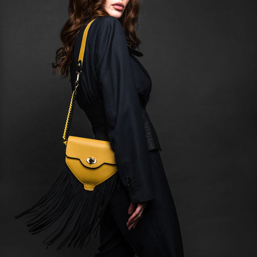 Woman in black coat carrying a designer handbag with fringe in yellow leather