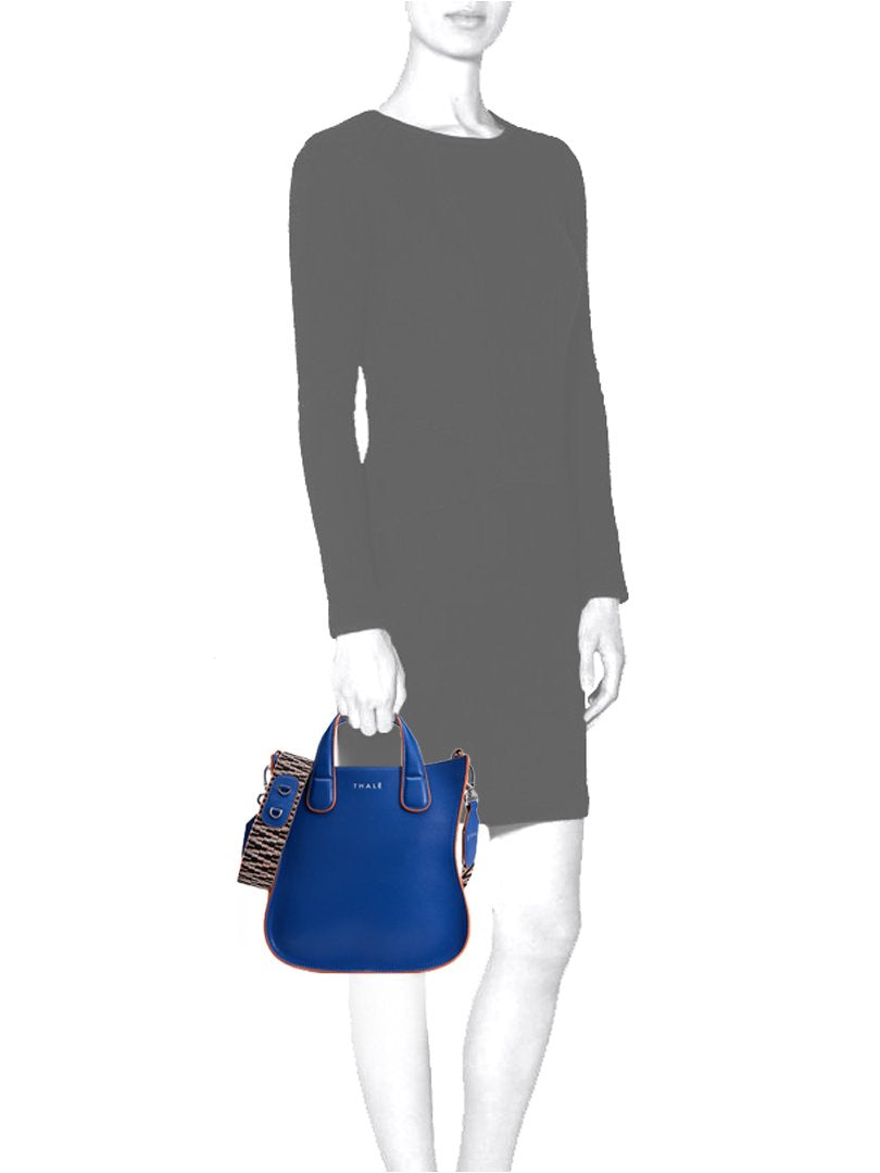 Mannequin carrying a monogrammed small tote handbag in blue leather