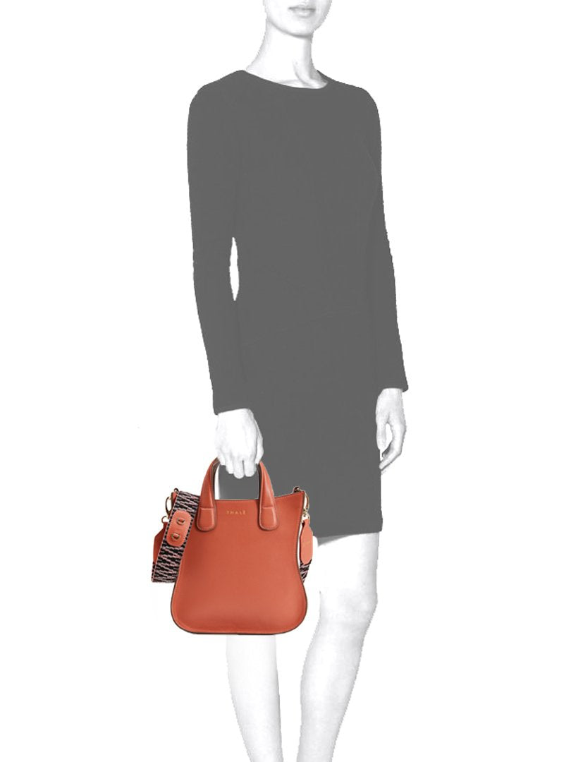 Mannequin carrying an orange leather small tote bag