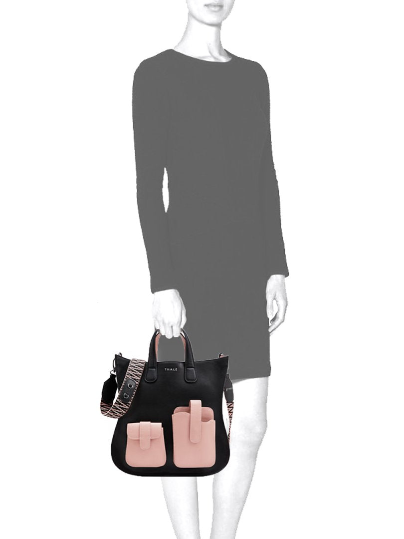 Mannequin holding a medium tote bag in black & pink leather