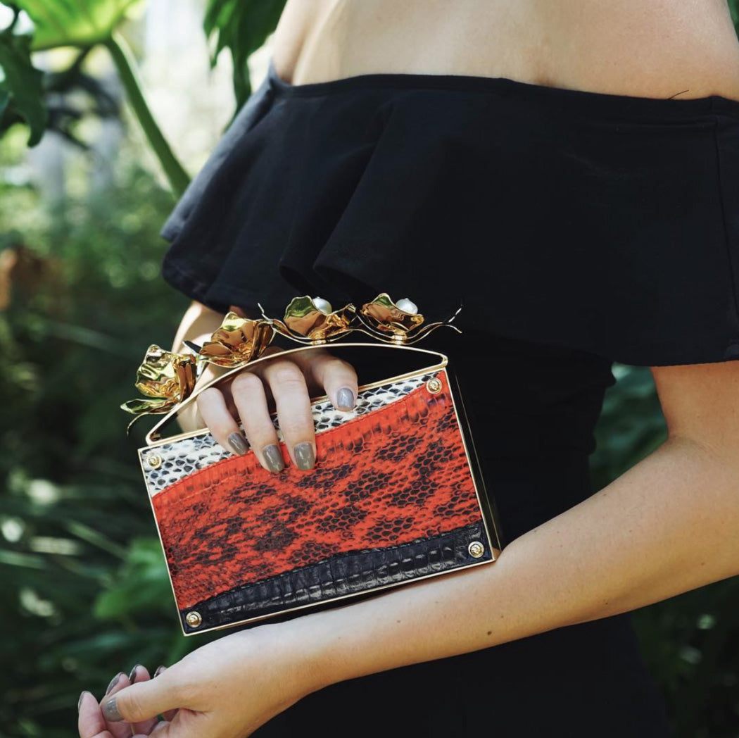 Woman in evening gown, holding red snakeskin designer clutch bag