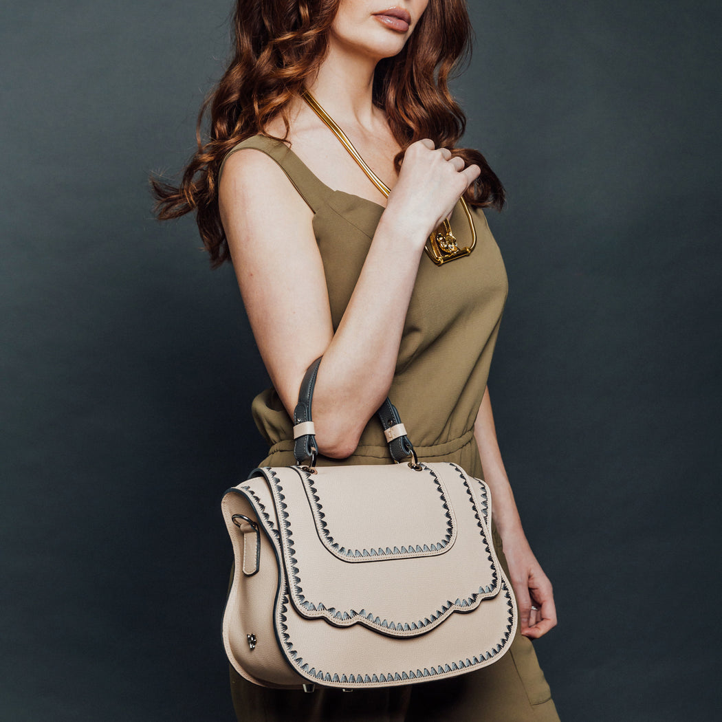 Woman holding designer satchel styled after the classic Audrey handbag
