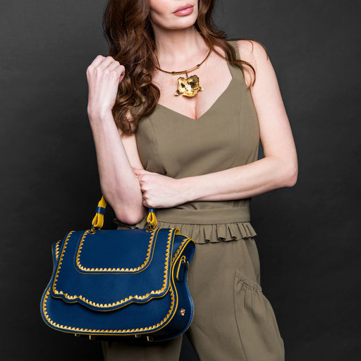 Woman holding Audrey handbag style designer satchel in blue leather with yellow stitching.