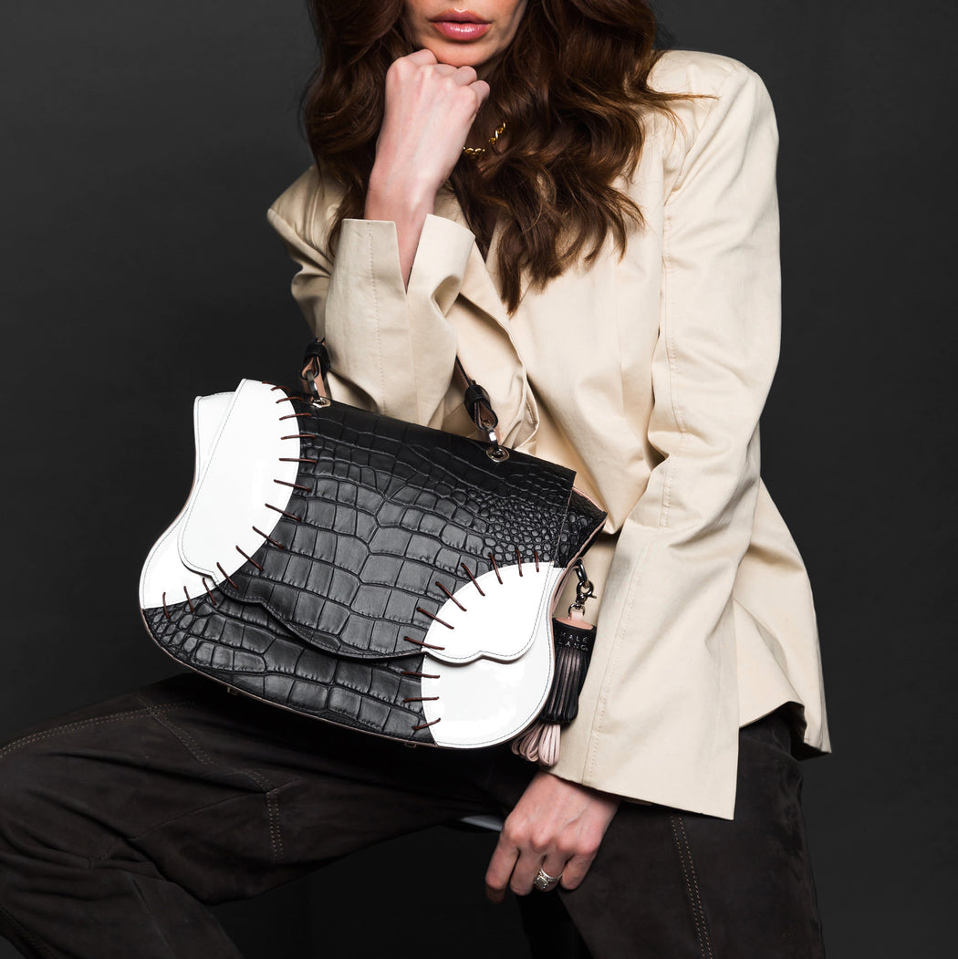 Woman holding baseball-inspired designer satchel bag.