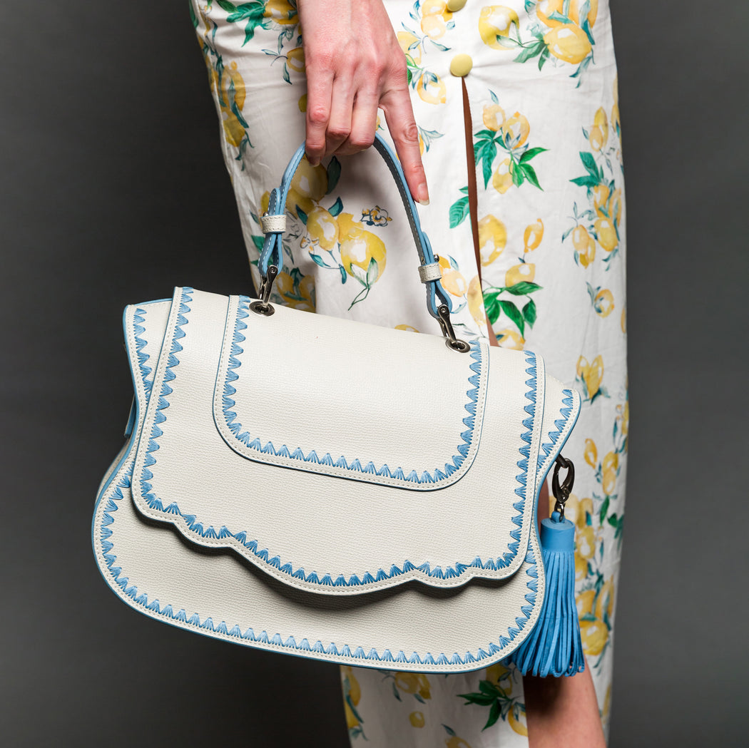 Woman holding white leather designer handbag