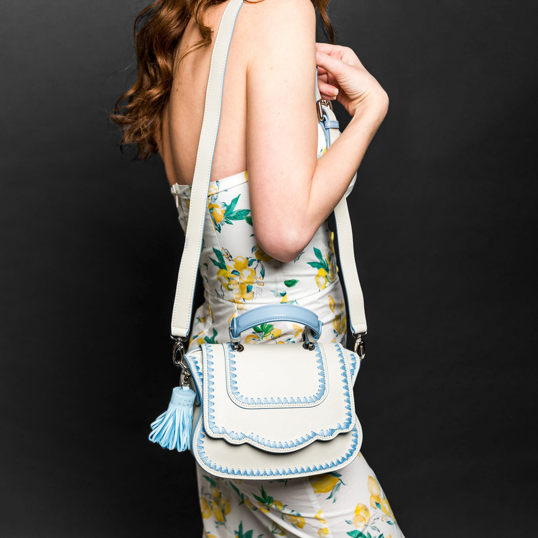 Woman holding white designer crossbody bag.