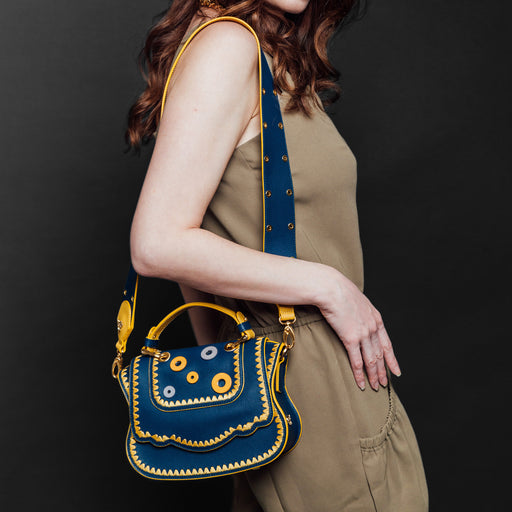 Woman wearing blue designer crossbody bag over the shoulder