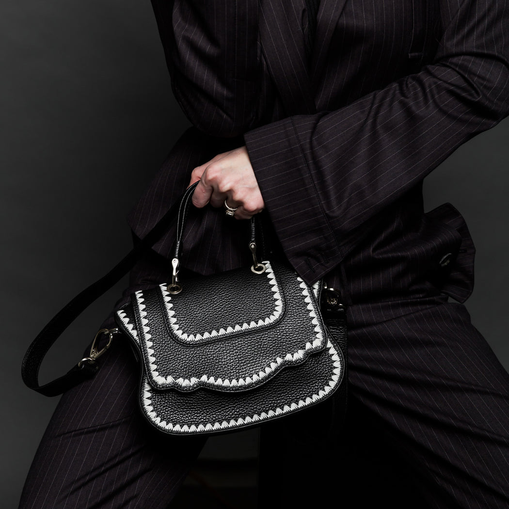 Woman holding black designer crossbody bag, mini.