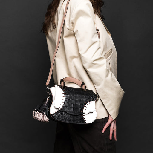 Woman carrying designer crossbody bag, mini, over the shoulder