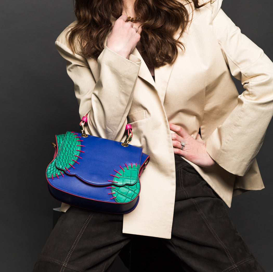 Woman holding a mini crossbody bag made of blue Italian leather with green accents