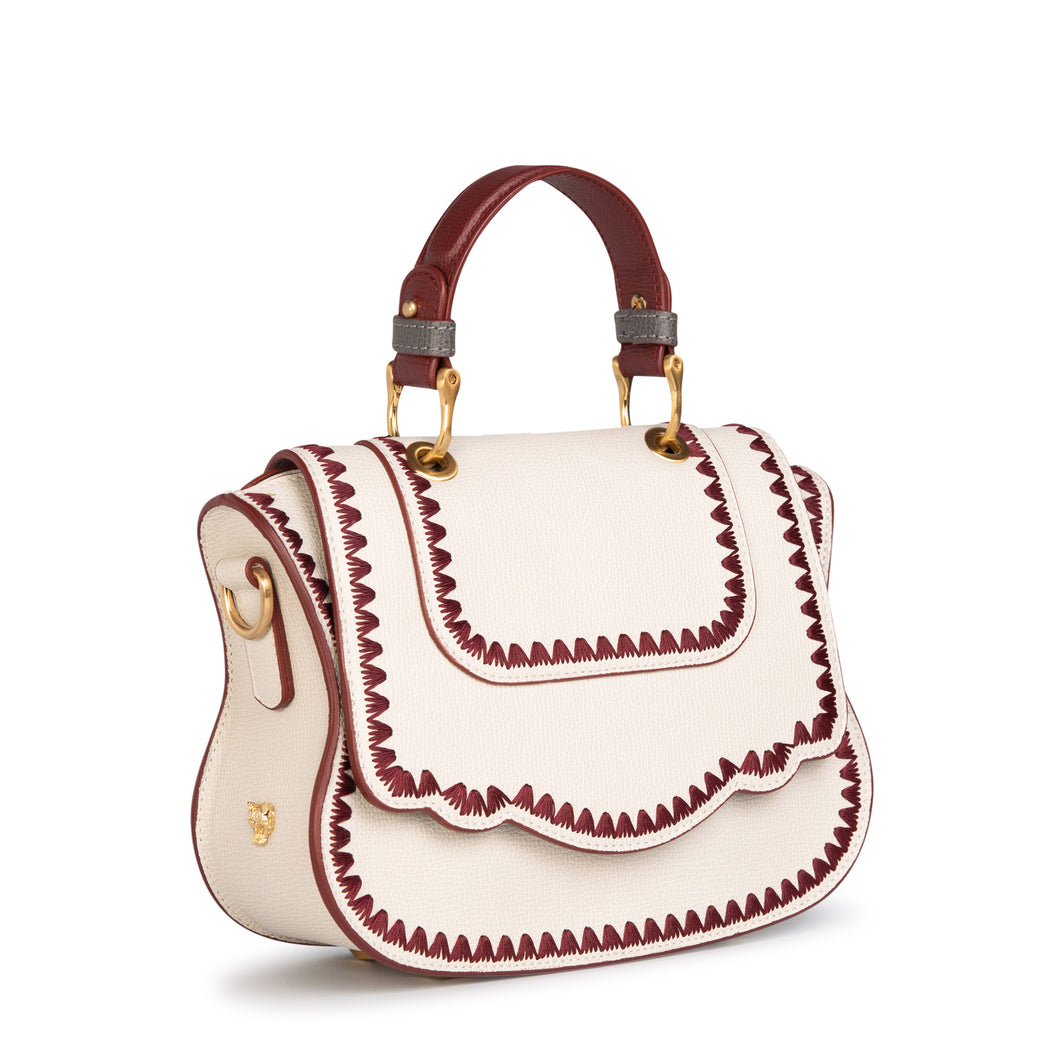 Women's designer handbag in white leather with red stitching