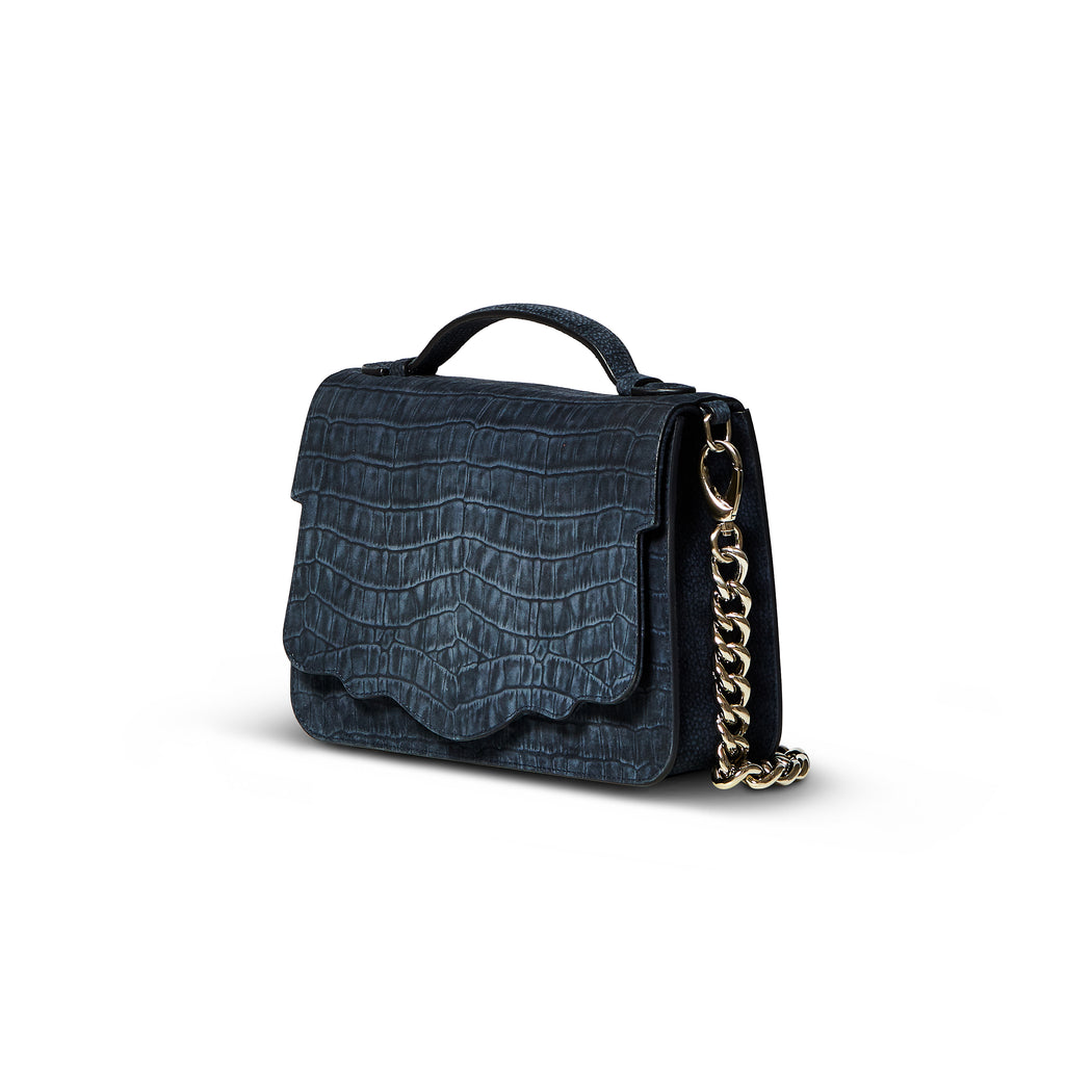 This best-selling top handle luxury leather bag in denim sueded calfskin with all-over textured crocodile print features both a detachable crossbody leather strap and a detachable chain strap. Make it your own with a fur Duma Hok-Pom or our signature leather tassel or opt for one of our leather guitar straps for an on-trend look. It is one of the easiest to accessorize handbags.
