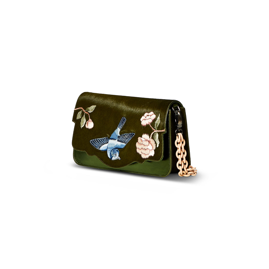 The Audreyette Small Couture luxury handbag can be worn a number of different ways. This green silk pony and green smooth calf leather bag features a powder-coated chain with detachable fur detail, embroidered floral and bird motif, and can be worn as a crossbody with detachable strap. It is one of the easiest to accessorize handbags.