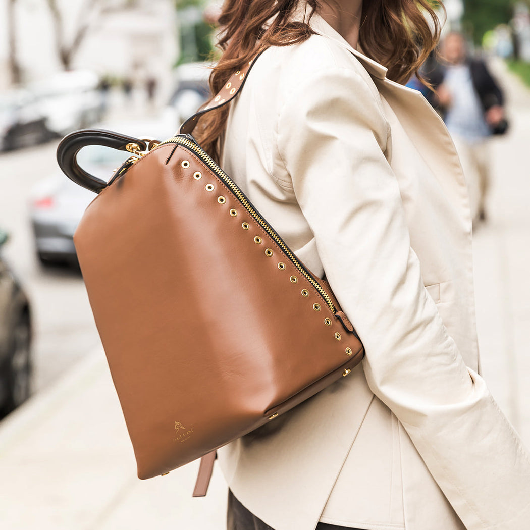 Woman wearing a brown leather backpack with racerback straps