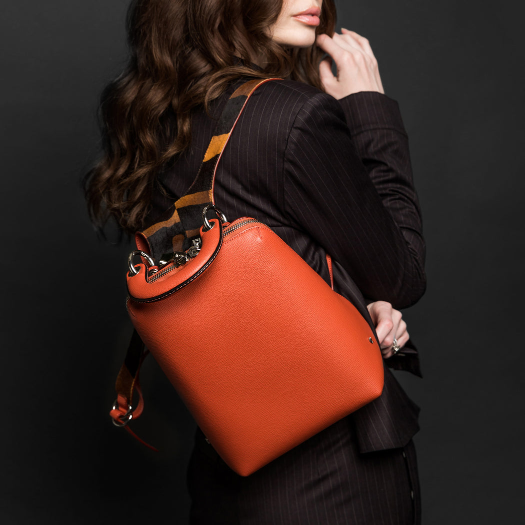 Designer mini backpack in orange leather, slung over a woman's shoulder