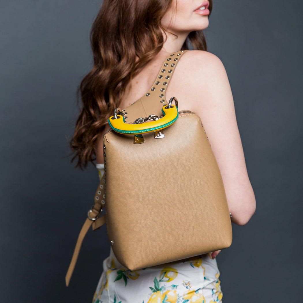 Beige leather designer backpack, small, slung over a woman's shoulder