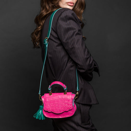Woman wearing micro designer shoulder bag with croc-embossed leather