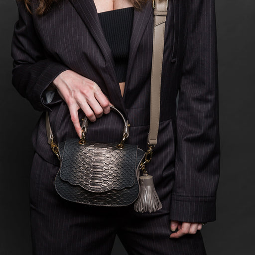 Woman holding designer crossbody bag, mini, in pewter snakeskin print leather