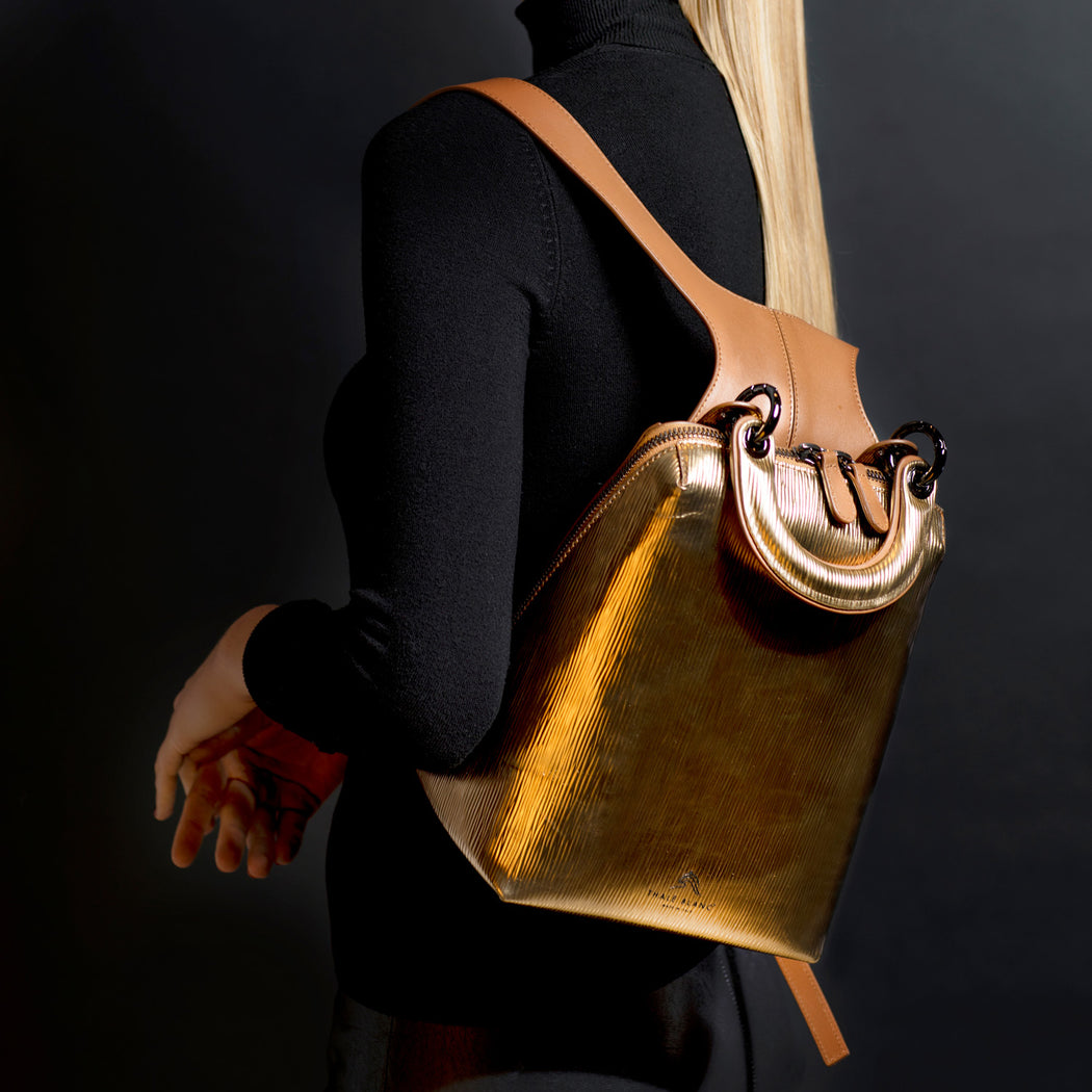 Small designer backpack in metallic gold leather, slung over a woman's shoulder