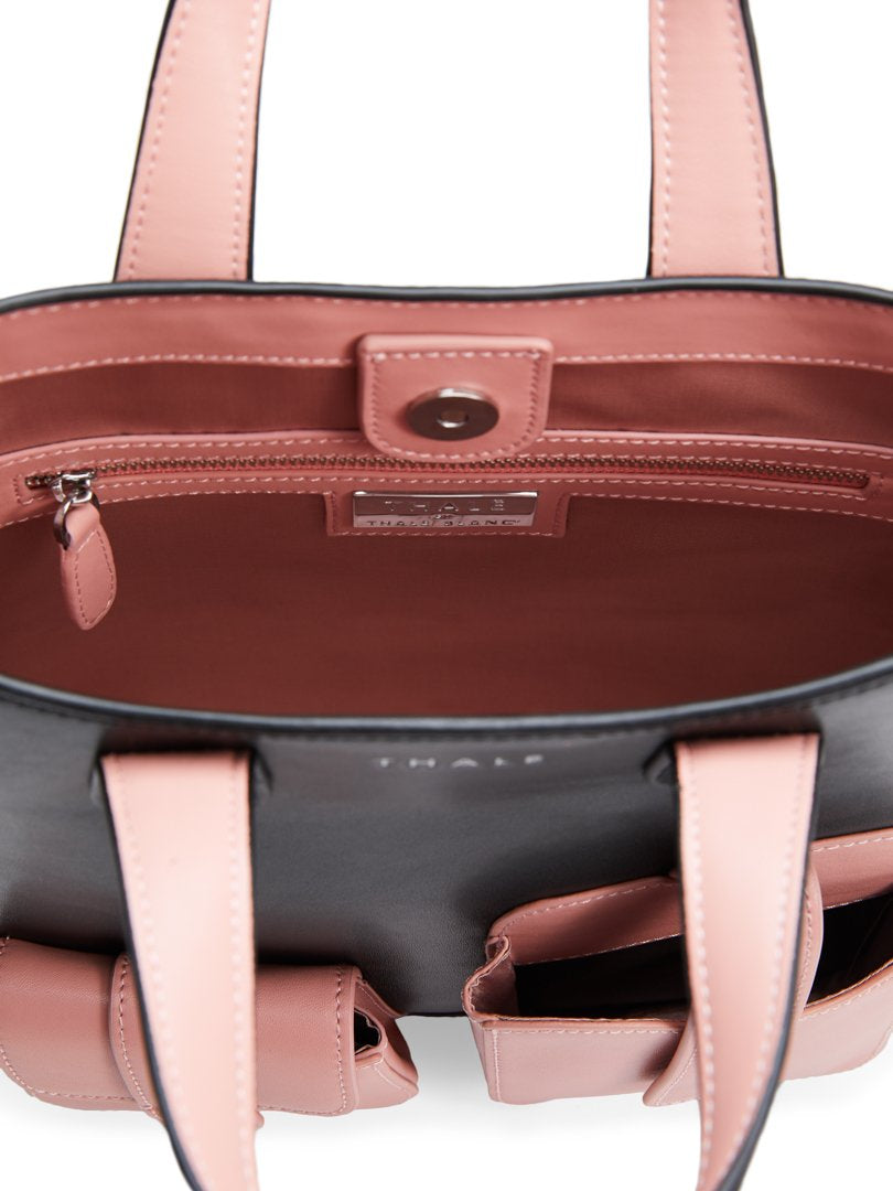 Interior pink lining of a black designer tote bag