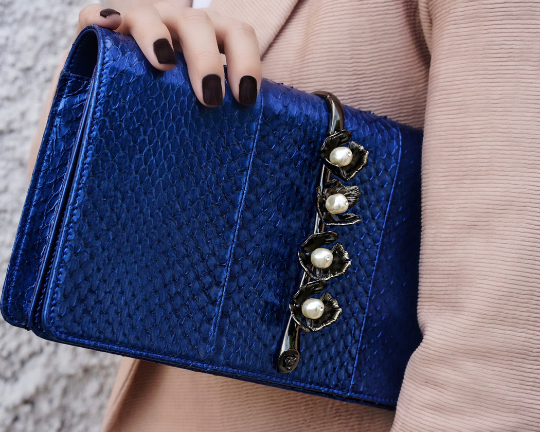 This fold-over style luxury clutch bag in cobalt elaphe is a smaller size, sitting upon a beautiful brass vine and embellished with elegant pearl stones. This roomy clutch is comfortable to hold as shown and easily fits everything you need. Great as an everyday bag. Magnetic top closure. Handmade in Italy.