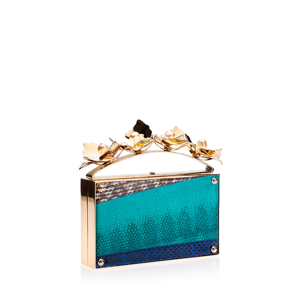 This luxury box clutch in Turquoise Watersnake is wrapped in snake in a graphic pattern with the top handle adorned with blooming custom brass orchids and elegant pearl stones. Designed to fit just the essentials. Handmade in Italy.