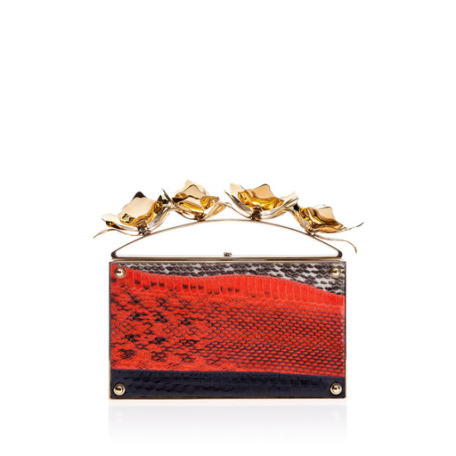 This luxury box clutch in Coral Watersnake is wrapped in snake in a graphic pattern with the top handle adorned with blooming custom brass orchids and elegant pearl stones. Designed to fit just the essentials. Handmade in Italy.
