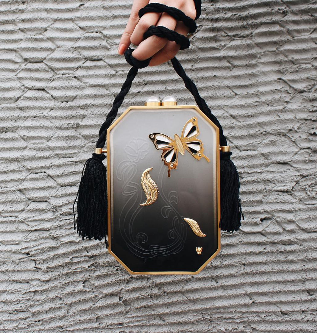 The luxury clutch in black ombre plexiglass with a cause. 20% of proceeds go directly to Children's Hospital Los Angeles with each purchase to support pediatric cancer research. With 3D brass ornaments, laser-cut engravings & a woven silk handle, it's a must own piece. Designed to fit just the essentials.
