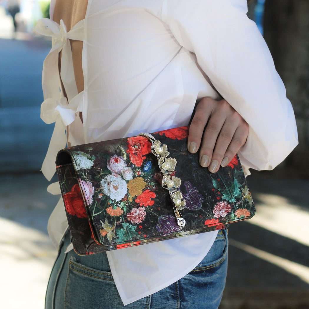 Woman holding a floral silk evening clutch bag