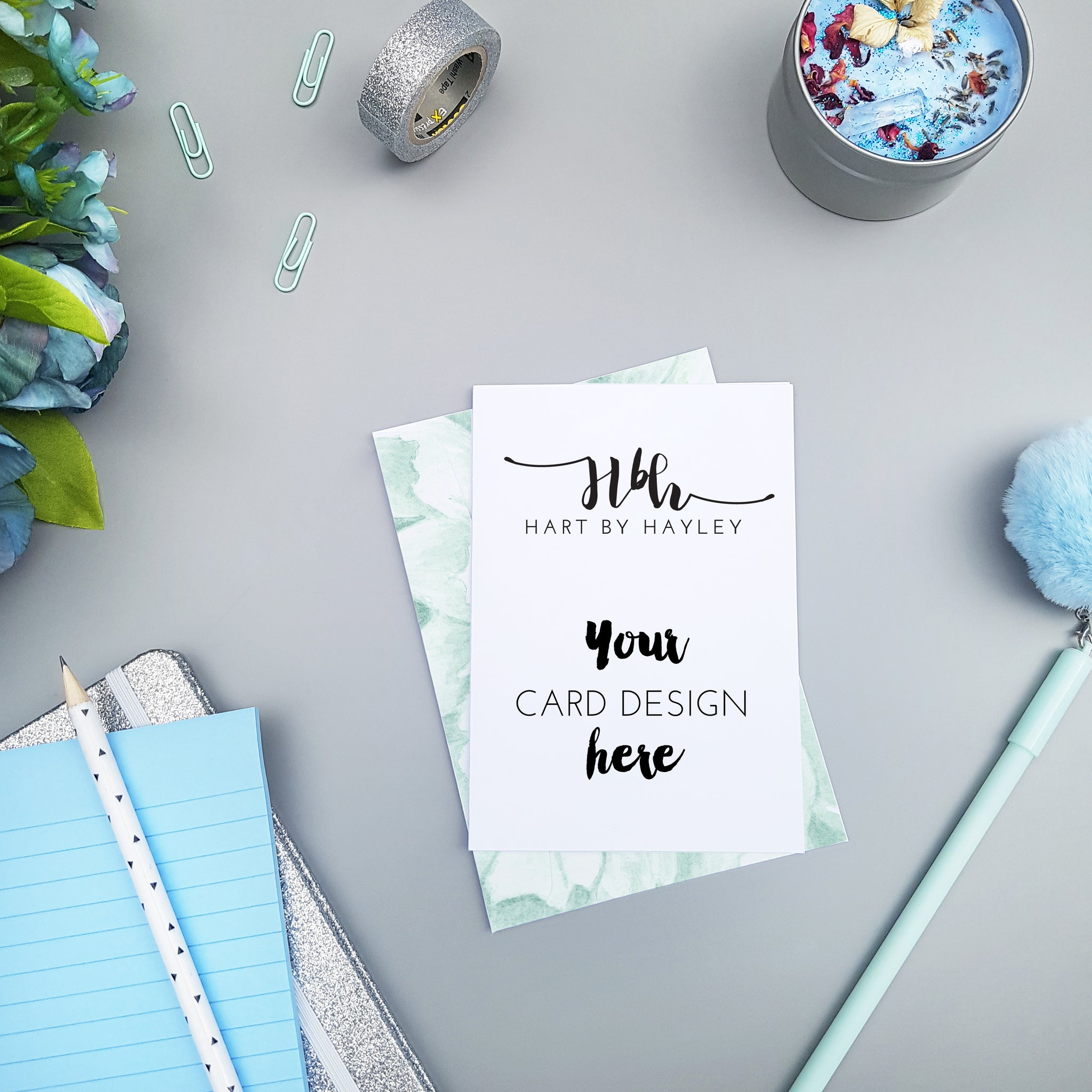 Card mockup on a grey desk with pops of blue