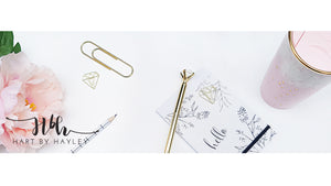 White desk Banner with pink and gold accessories.