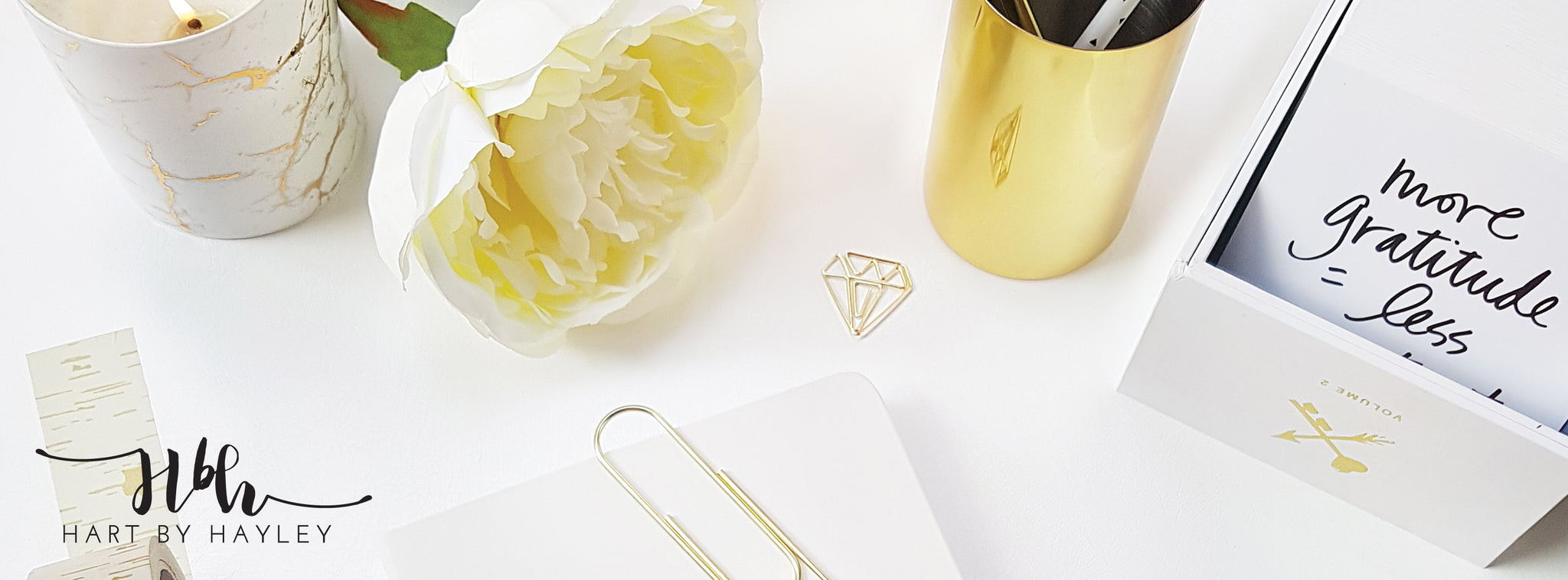 Relaxing white desk banner with gold accessories.