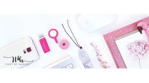 White desk Banner with pink accessories.