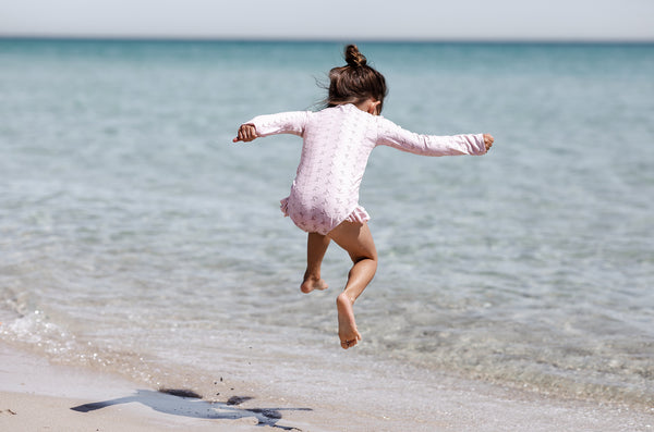 Girl jumping at beach wearing Willow Swim Sophia embroidery swimsuit