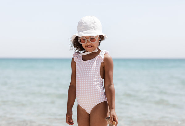 Girl on beach wearing Willow Swim childrens swimsuit hat and sunglasses