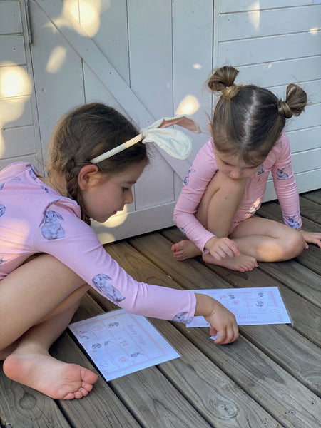 Girls playing Easter bingo game in garden cubby house