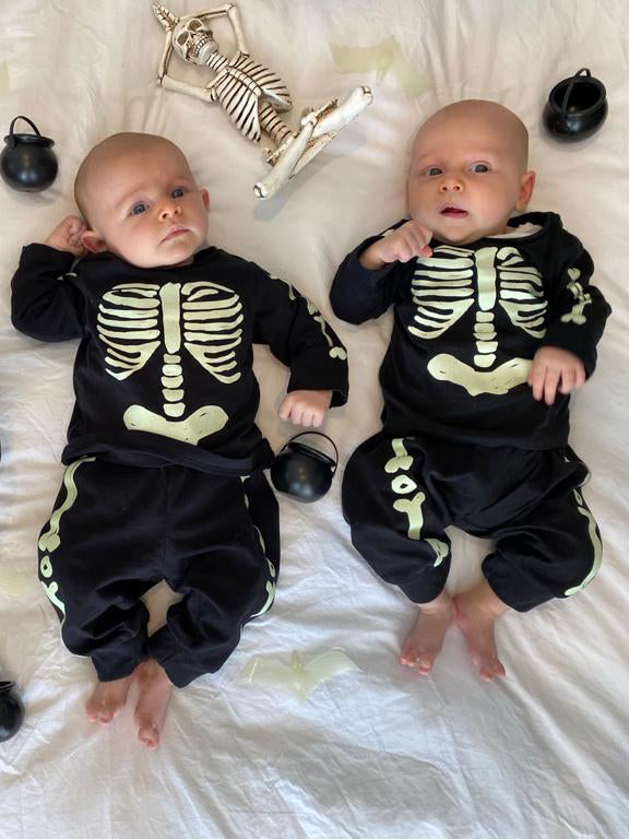 Baby boys wearing Halloween skeleton costumes