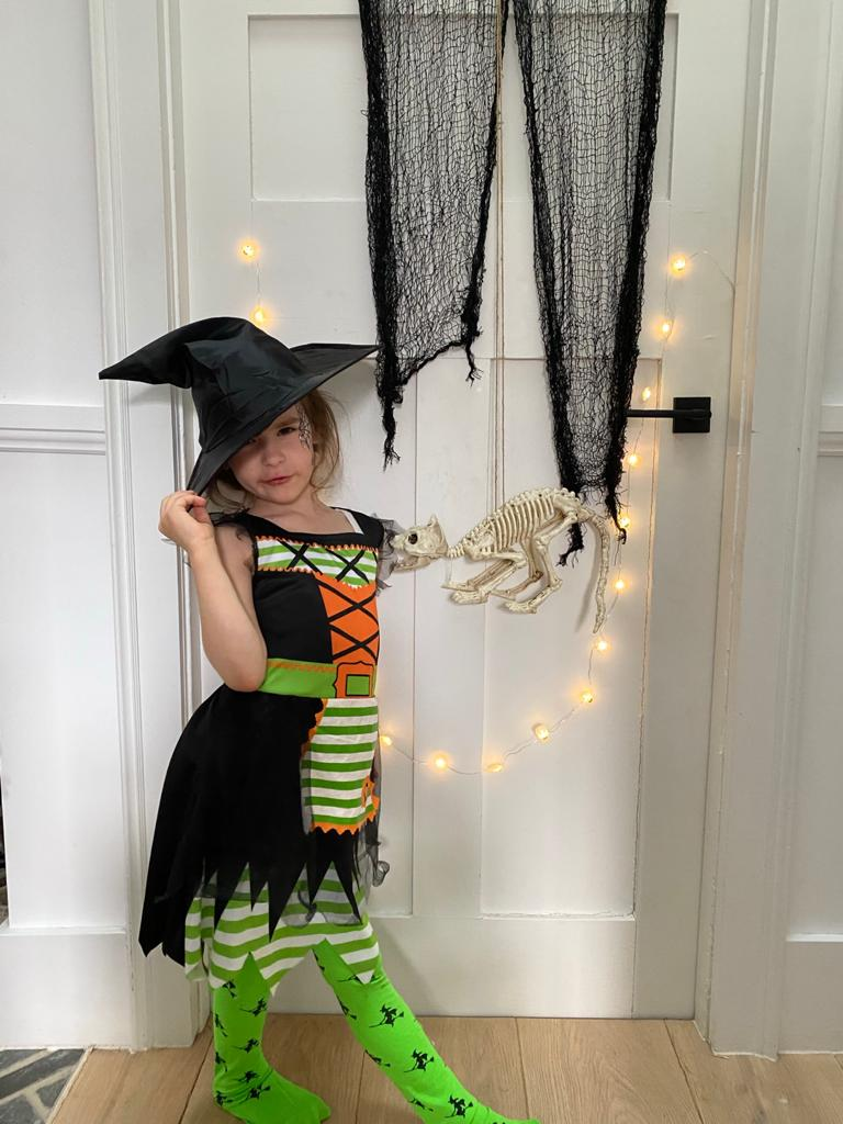 Little girl dressed up as witch at home for Halloween