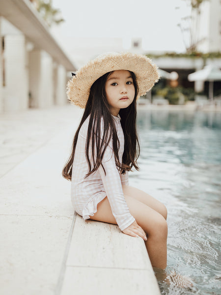 Little girl at Calile Hotel pool wearing Willow Swim Sophia in peachy gingham