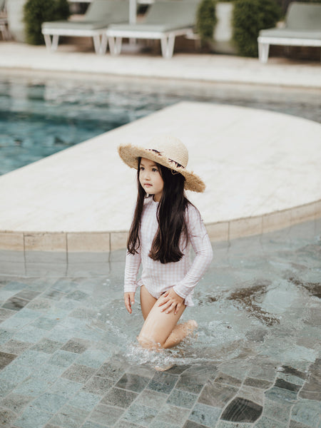 Little girl wearing Willow Swim Sophia swimsuit playing in pool Calile Hotel