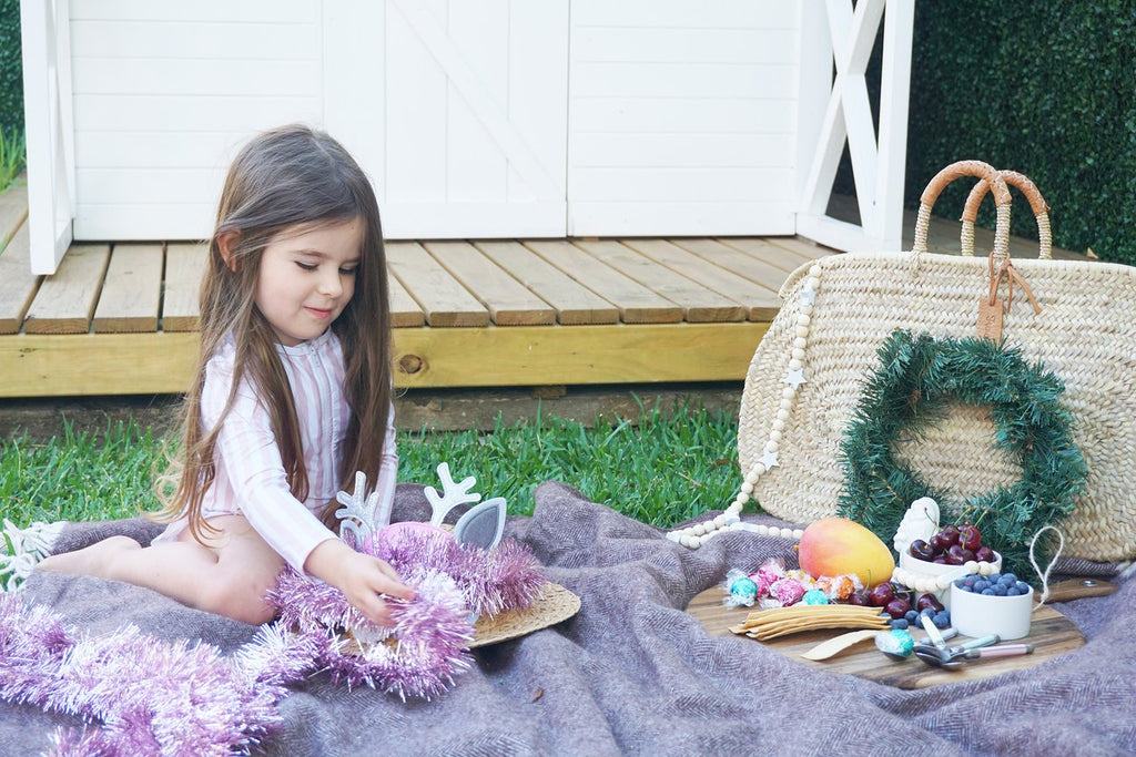 Little girl in garden with picnic decorating christmas hat wearing Willow Swim kids swimwear