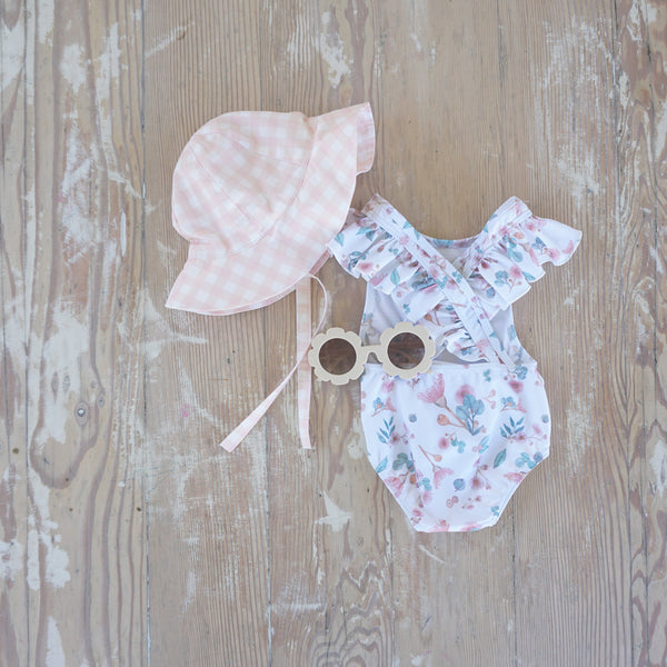 Willow Swim Lulu girls sunglasses in Blush lifestyle shot with hat and swimming costume