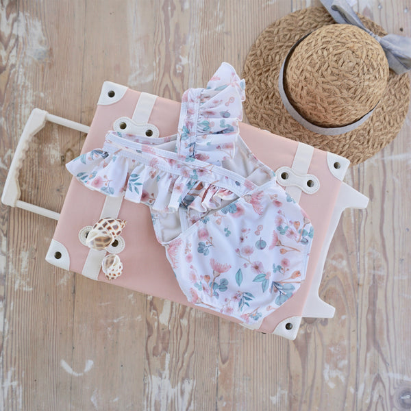 Willow Swim Gracie girls swimsuit in gumnuts lifestyle shot with suitcase and hat