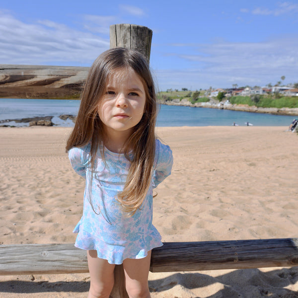 Little girl at beach wearing Willow Swim Allegra two-piece girls swimsuit in Spring Floral