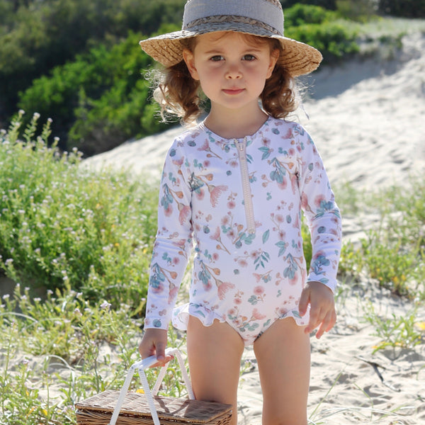 Little girl at beach wearing Willow Swim Sophia girls swimsuit in Gumnuts
