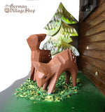 German Cuckoo Clock battery operated black forest chalet with see saw and music - close up of deer