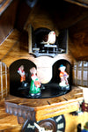 German Cuckoo Clock battery operated black forest chalet with wood sawyer men and music - close up of cuckoo bird