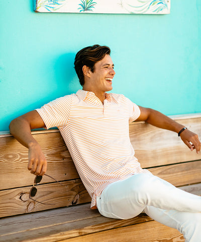 A man sitting on a bench in a Southern Tide striped polo and white khaki pants.