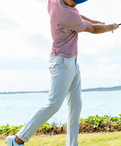 A man in a Southern Tide striped polo and khaki pants swinging a golf club.