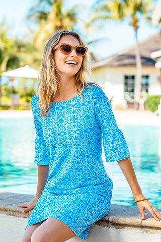 woman wearing a blue printed dress by a pool as a bridal shower look
